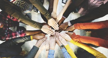 Diverse group of hands coming together in a circle, colorful