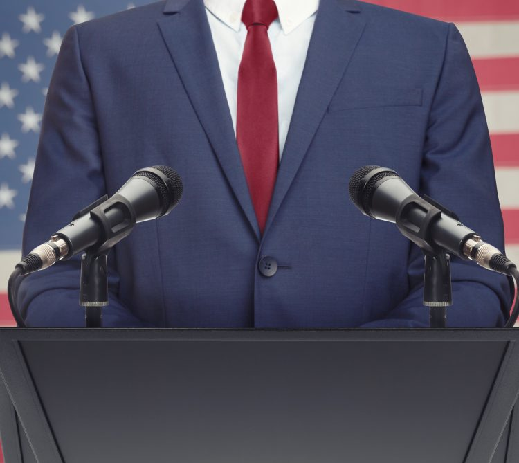 Politician in suit standing at podium with American Flag background