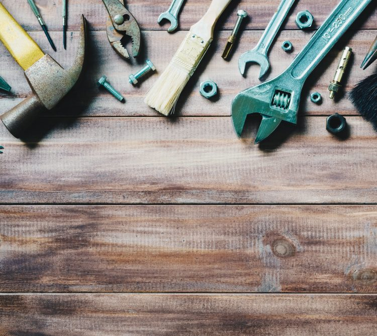 Assorted tools on wood background