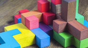 Multi-size and shaped colored wood blocks stacked randomly on wood surface