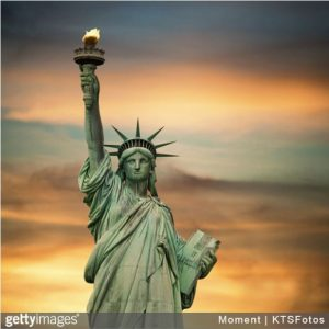Statue of Liberty with sun setting in the background