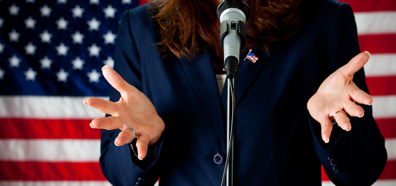 Woman politician standing at microphone with American flag in background